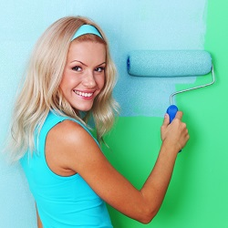a lady using a paint roller to paint a wall blue